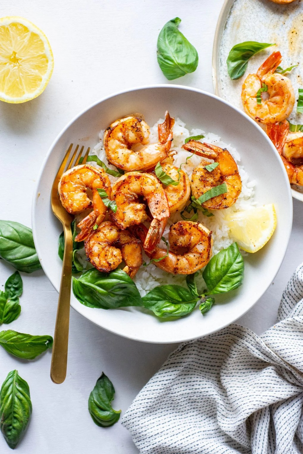 Large white bowl with white rice topped with seared shrimp with fresh basil and lemon wedges on a light background