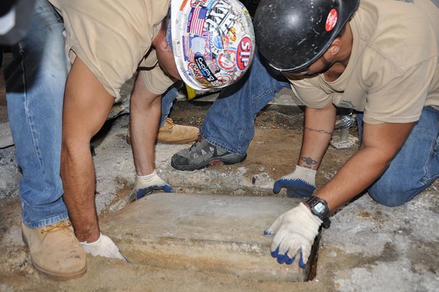Construction workers lift the capsule out of the ground.