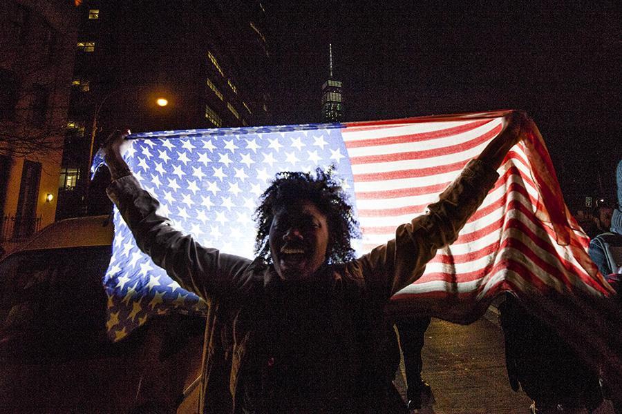 A woman waves an American flag.