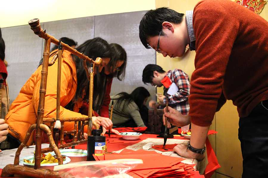 Wu Ke helps students practice their calligraphy during the Chinese New Year event.