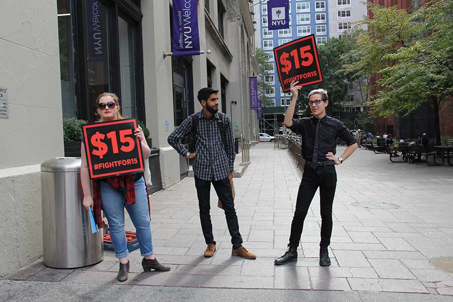 Haley Quinn, Vishnu Bachani, and Aaron Petykowski (from left to right) of NYU's Student Labor Action Movement (SLAM) protest in front of the NYU Welcome Center on Friday, Oct. 9, 2015, advocating a raise in student worker pay to $15 an hour.
