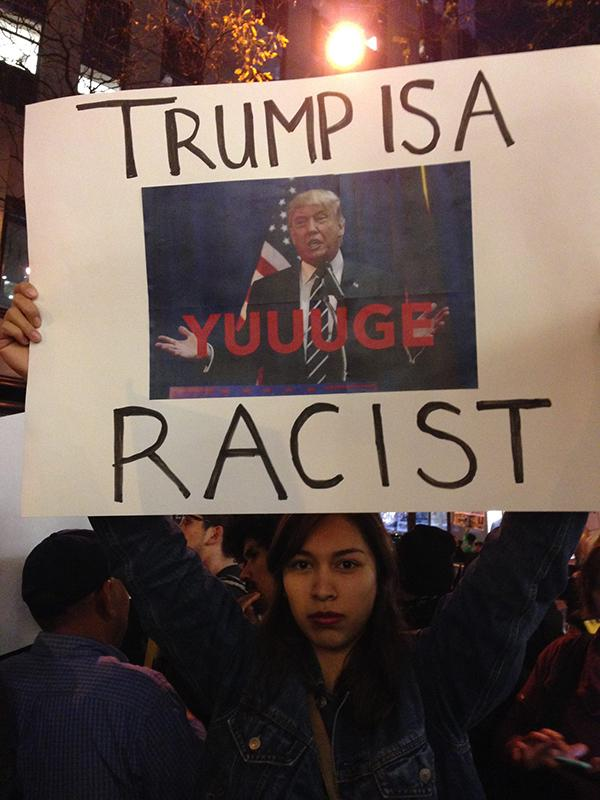 NYU Dream Team protester holds a sign at 30 Rockefeller Center in retaliation to Donald Trump's appearance on Saturday Night Live.
