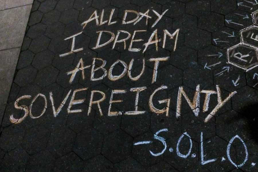 The NYU Native American and Indigenous Students Group protested in Washington Square Park with posters and sidewalk chalk.