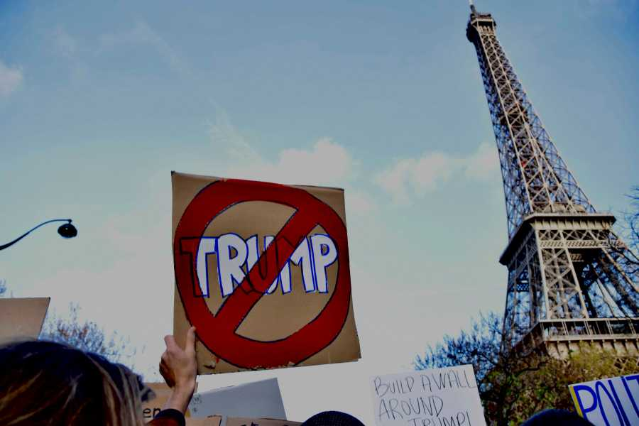 A protester raises her anti-Trump sign near the Eiffel Tower during a rally on Saturday.