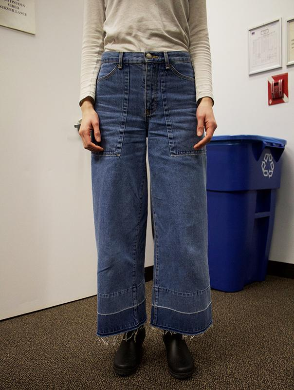 This pair of wide leg jeans is paired with a light colored top and short, black rainboots for an effortless, put together look. The high waisted style extends the legs.