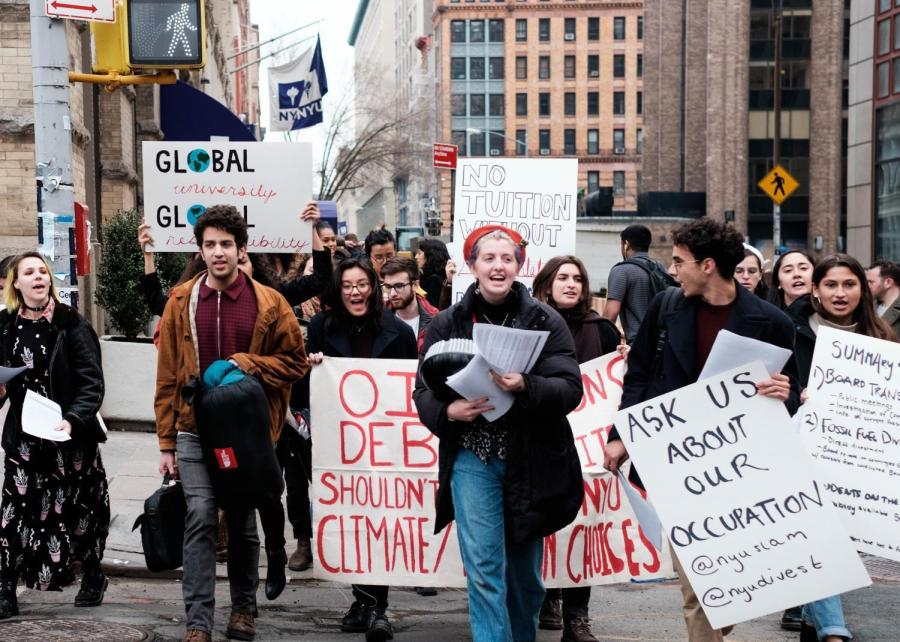 Demonstrators marching from the Admissions Center to the Kimmel Center for University Life yesterday, chanting and handing out flyers outlining their demands to passersby.