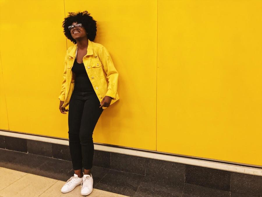 NYU Madrid student Laurie Germain beside the iconic yellow walls of the Madrid  metro.