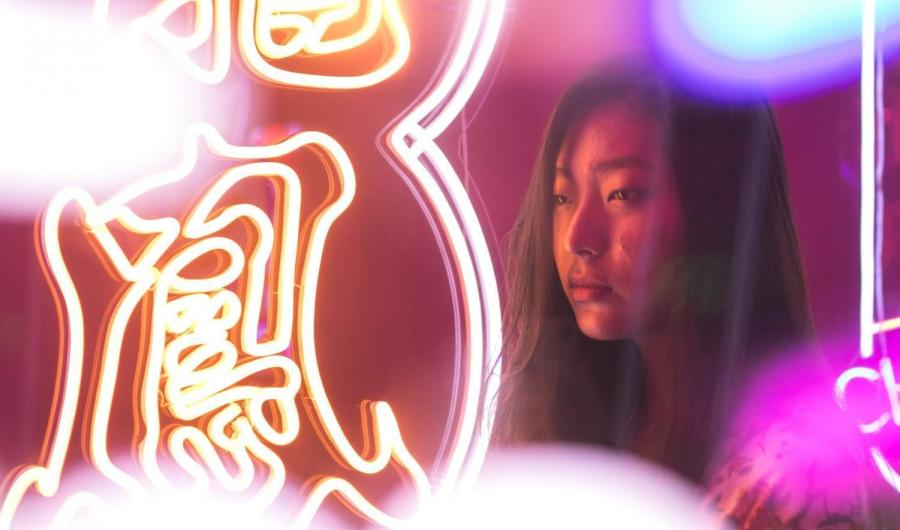 A visitor stands among the neon signs.
