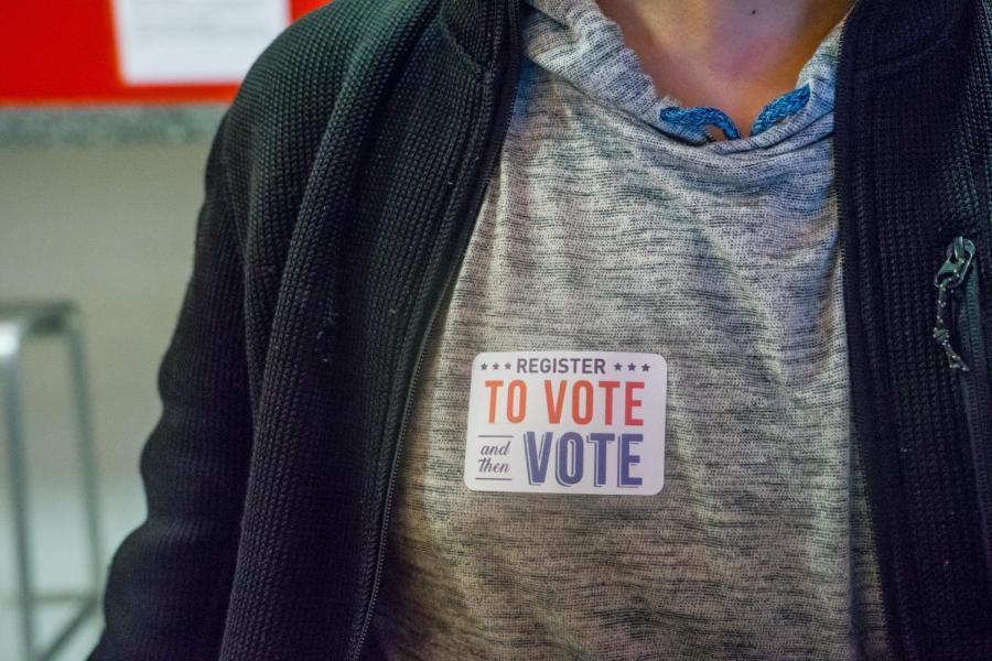 A volunteer wears a sticker saying