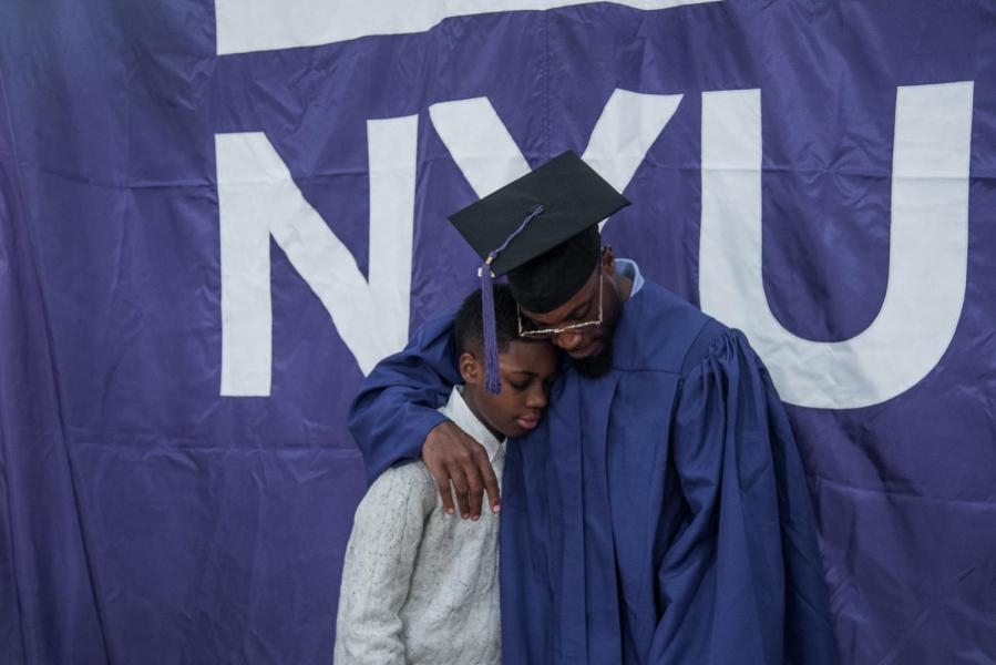 Jermaine Haywood with his son, Jermaine Jr., after receiving his diploma through NYU's Prison Education Program. (Photo by Sam Klein)