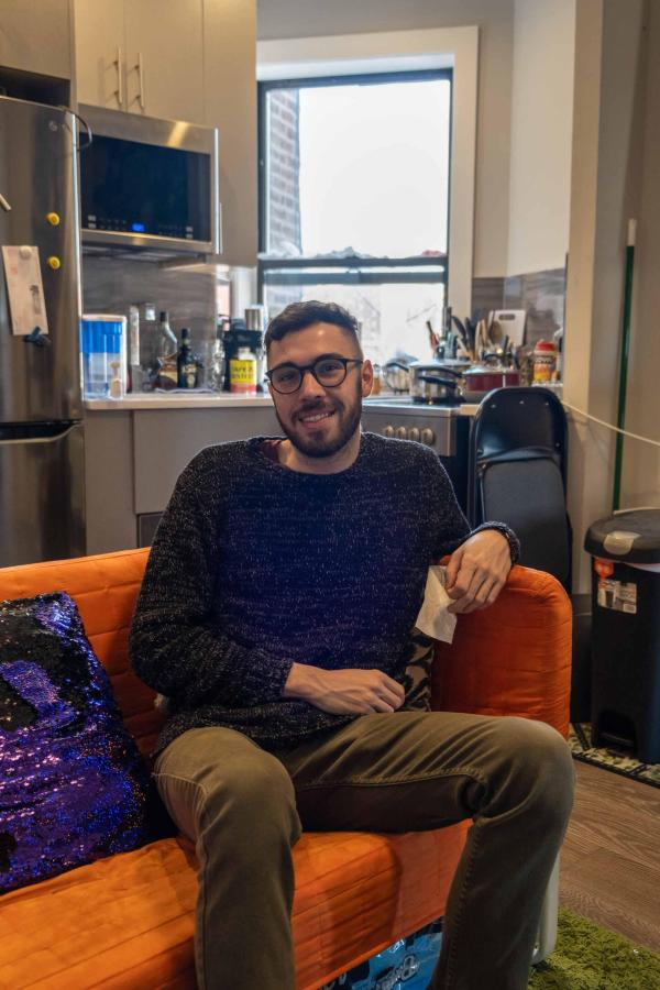 Michael Marinaccio sits on his sofa in his apartment in Spanish Harlem. One day he hopes to move further downtown — preferably to a studio in Midtown. (Photo by Justin Park)