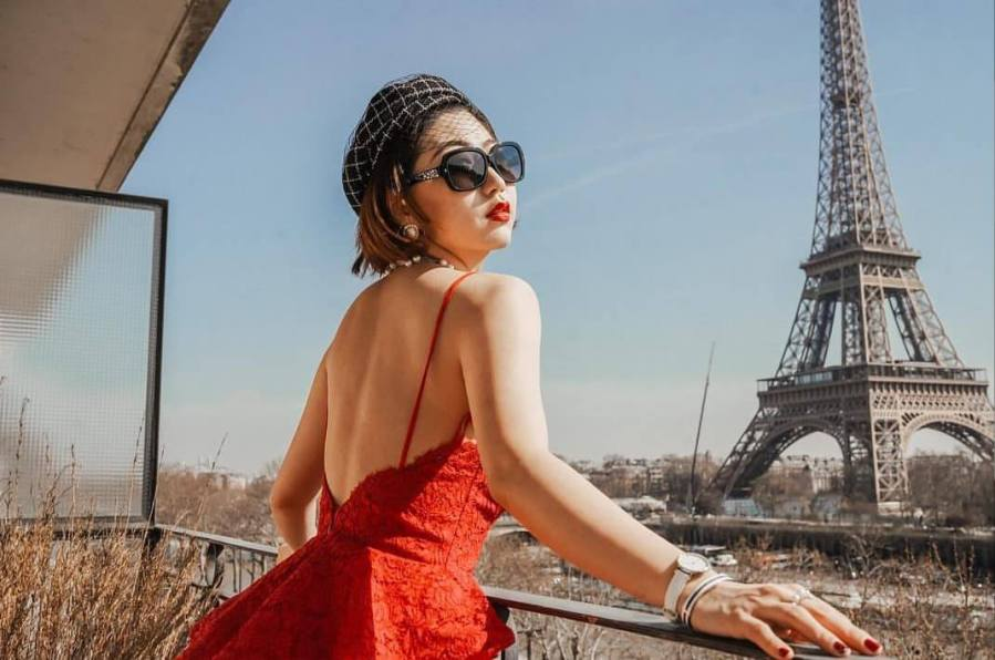 Candice Wu, a Stern graduate student, dons a stunning red dress, a splash of color amidst the rustic Paris background. (via Instagram)