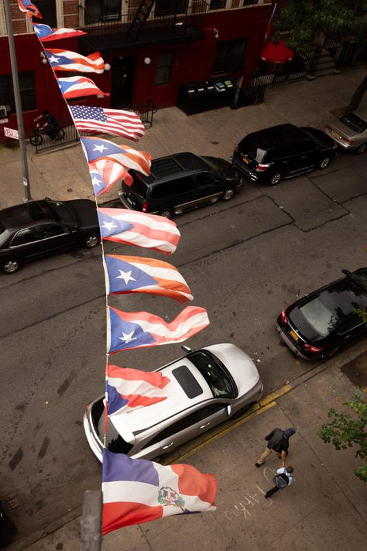 People walk under Puerto Rican and American flags hanging from an apartment building in East Harlem. (Staff Photo by Alina Patrick)