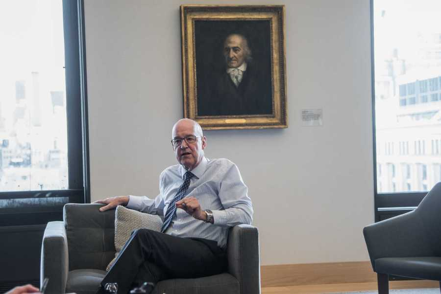 NYU President Andrew Hamilton in front of his office painting of university founder Albert Gallatin. (Photo by Sam Klein)