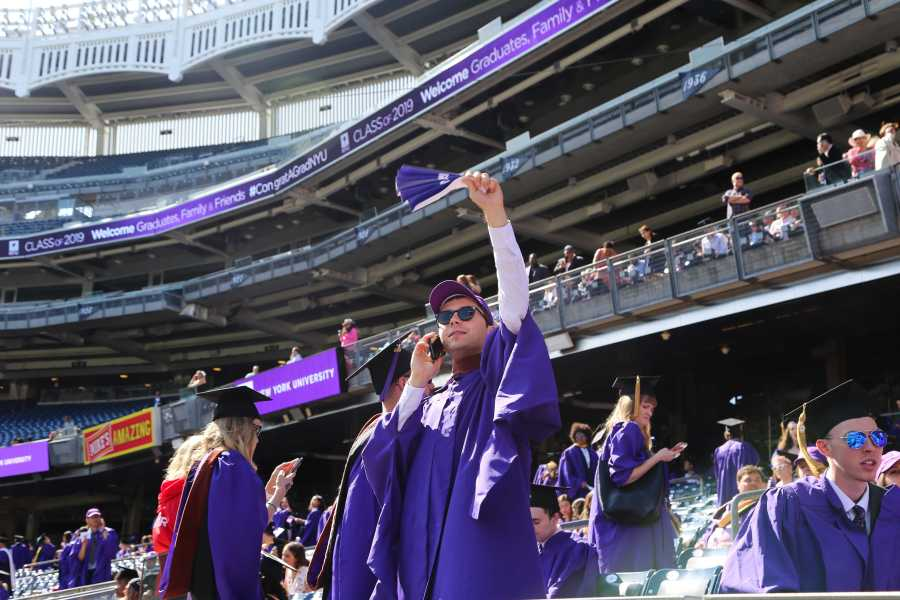 An NYU graduate, wearing his violet gown and a 2019 commencement cap, talks on the phone and waves the commencement program which he has folded into a fan. (Photo by Julia McNeill)