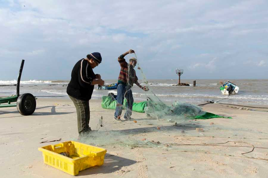 A+woman+and+a+man+untangle+the+fish+from+the+net+and+place+the+fish+in+the+basket+to+sell+or+eat+later.+The+day%27s+catch+brought+in+multiple+nets+that+have+to+be+detangled.+%28Photo+by+Taylor+Bissey%29