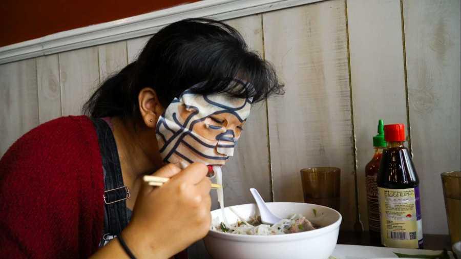 Marva Shi, our deputy multimedia editor, slurps up a bowl of pho in Saigon Shack while wearing a Gudetama pancakes facemask. (Staff Photo by Min Ji Kim)