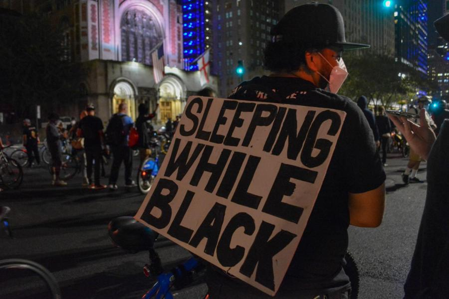 A protester hangs a sign on their back reading