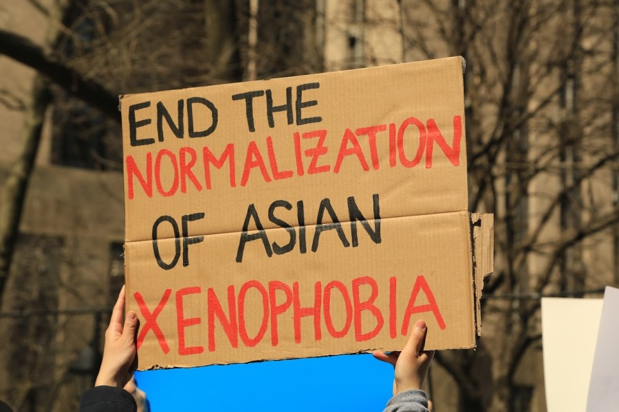 """A protester holds up a sign reading """"End The Normalization of Asian Xenophobia."""" (Photo by Suhail Gharaibeh)"""