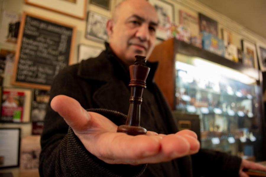 Imad Khachan presents a chess piece to the camera. Khachan owns Chess Forum in Greenwich Village on Thompson. (Staff Photo by Manasa Gudavalli)