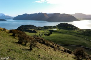 "Looking down at Lake Wanaka, with what William dubbed ""One Tree Hill"" off to the right. A little stream leads through the sheep pasture."