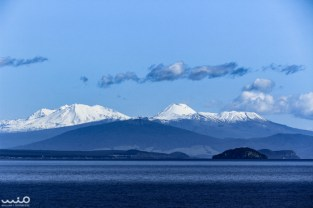 Across Lake Taupo, you can see the three main volcano peaks of Tongariro National Park. From left to right: Mt Ruapehu, Mt Ngauruhoe, and Mt Tongariro. Lake Taupo itself it a volcanic caldera.