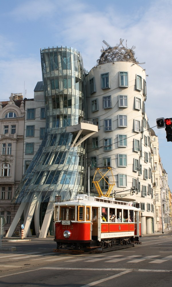 Dancing house in prague with red tram - NZMuse