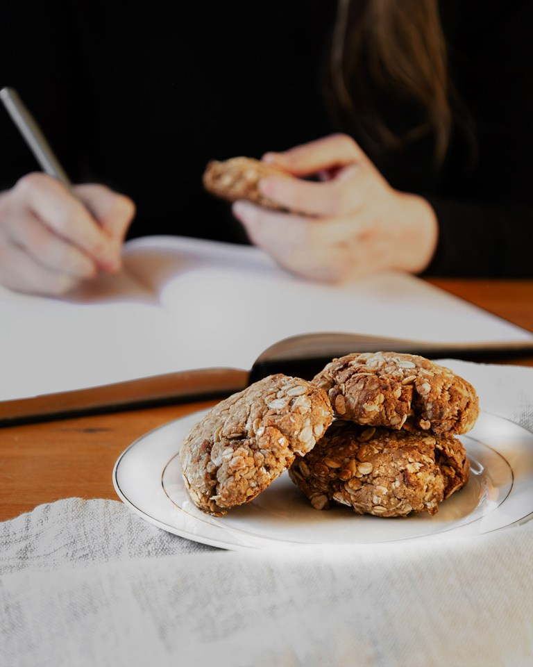 Plate of oat cookies in front of woman writing in book