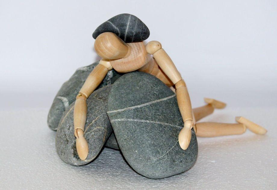 石に押しつぶされる人形