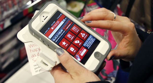 FILE - In this Friday, Nov. 23, 2012, file photo, Tashalee Rodriguez, of Boston, uses a smartphone app while shopping at Macy's in downtown Boston. For the first time, analysts predict more than half of online traffic to retailer sites will come from smartphones than desktops during the busy Black Friday holiday shopping weekend. And though it�s still a small fraction of online revenue, mobile sales are jumping too. Larger phone sizes, improved retailer apps, more online deals and shoppers� increasing comfort with shopping online are driving the trend. (AP Photo/Michael Dwyer, File)