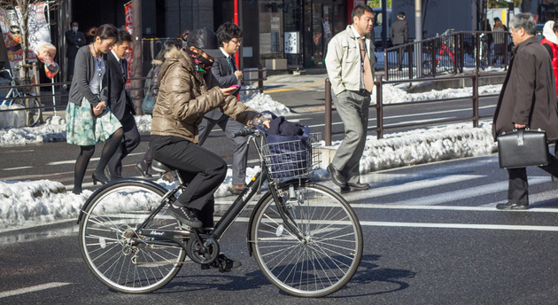 Japanese person checking a cellphone while on a bike