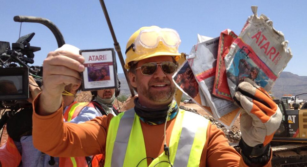 Excavators hold up E.T. for the Atari 2600