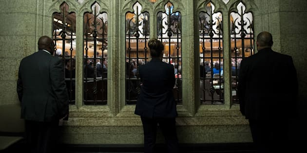People listen from outside the chamber in the House of Commons on June 29, 2016 in Ottawa.