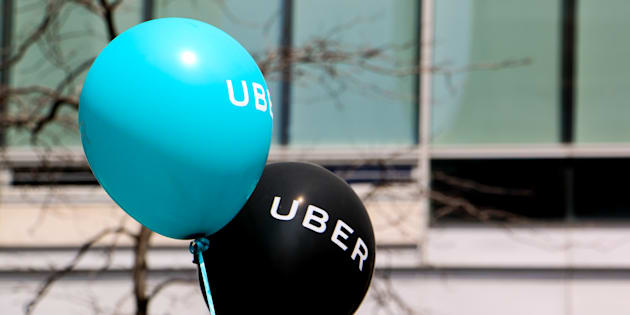 A blue and a black balloon are floating outside at a pro Uber rally April 29, 2016 in Montreal.