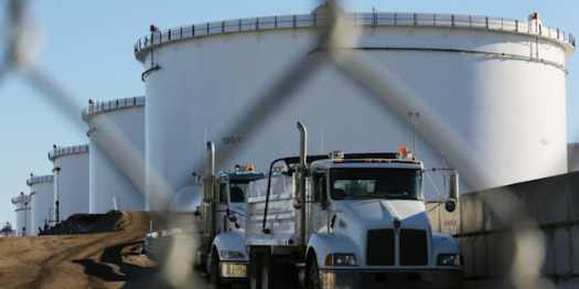 Dump trucks are parked near crude oil tanks at Kinder Morgan's North 40 terminal expansion construction project in Sherwood Park, near Edmonton on Nov. 13, 2016.