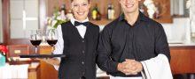 Portrait von einem Kellner und einer Kellnerin mit Wein im Restaurant