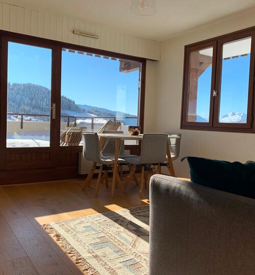 La pièce à vivre du Chèvrefeuille avec vue sur les montagnes et le domaine skiable