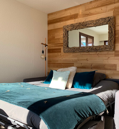 Le canapé-lit ouvert dans la pièce à vivre du Chèvrefeuille avec vue sur les montagnes et le domaine skiable