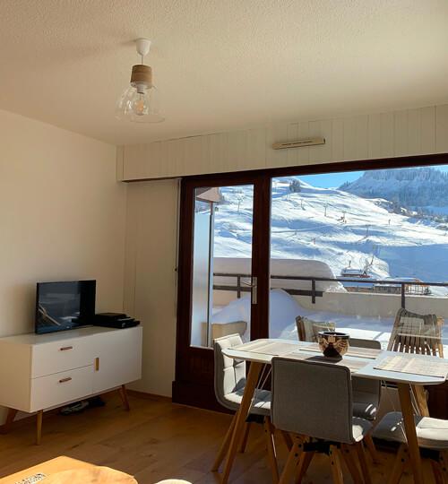 La pièce à vivre du Chèvrefeuille donnant sur la grande terrasse et la vue sur les montagnes et le domaine skiable