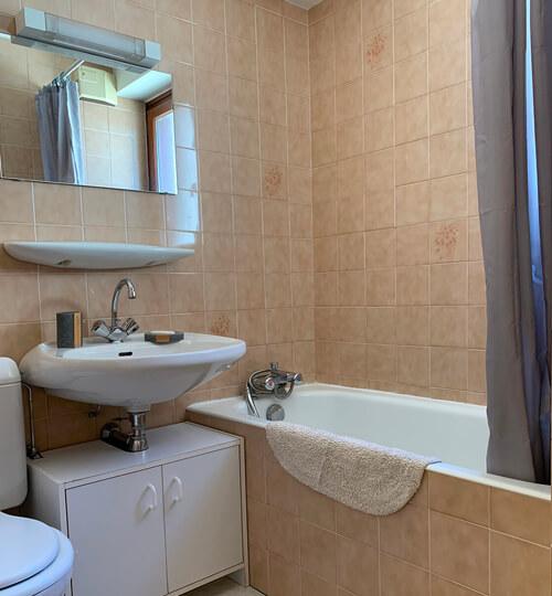 La salle de bain du Chèvrefeuille avec baignoire, WC et sa fenêtre sur l'extérieur