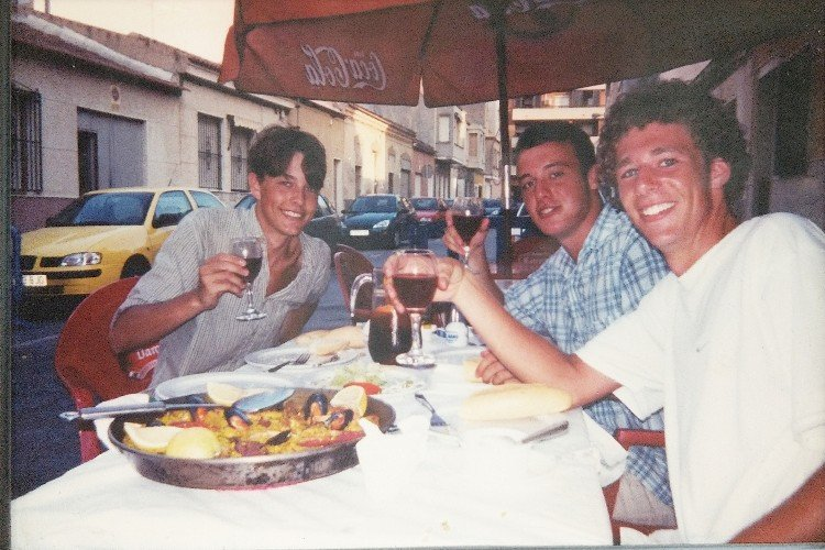 Three young men sitting around a pot of paella. Each holds up a glass of red wine.