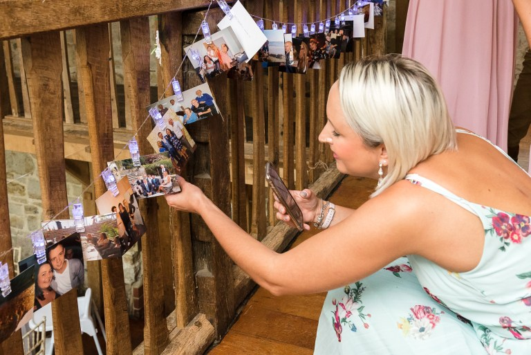 Wedding guest viewing photographs hung up on display at Swallows Oast wedding venue, Ticehurst, East Sussex | Oakhouse Photography