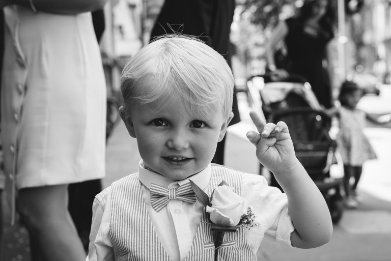 Young boy waiting for the wedding to start outside Chelsea Old Town Hall, King's Road, London | Oakhouse Photography