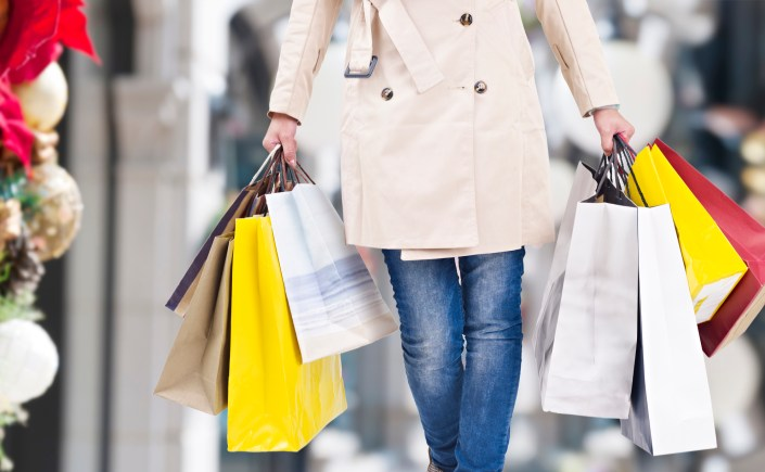A young woman walking with shopping bags in hands, christmas background