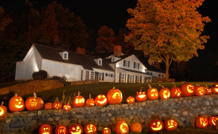 Jack O' Lanterns lined up on a stone wall on dark, fall night in front of the Van Hoosen Museum in Rochester Hills, MI.
