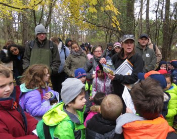A scout master hands out Cub Scout Adventure Day patches to a large group of scouts who are gathered around her.
