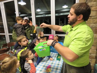 A nature educator holds up a green bucket with craft items and hands out baggies filled with craft items to the children gathered around him.