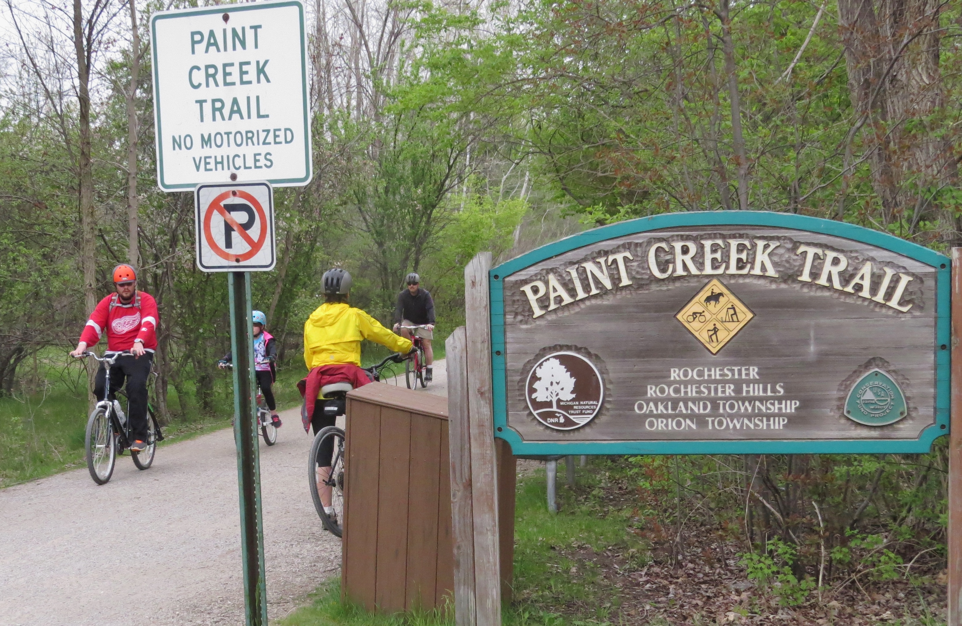 A wooden Paint Creek Trail sign next to the trail with bikers on it