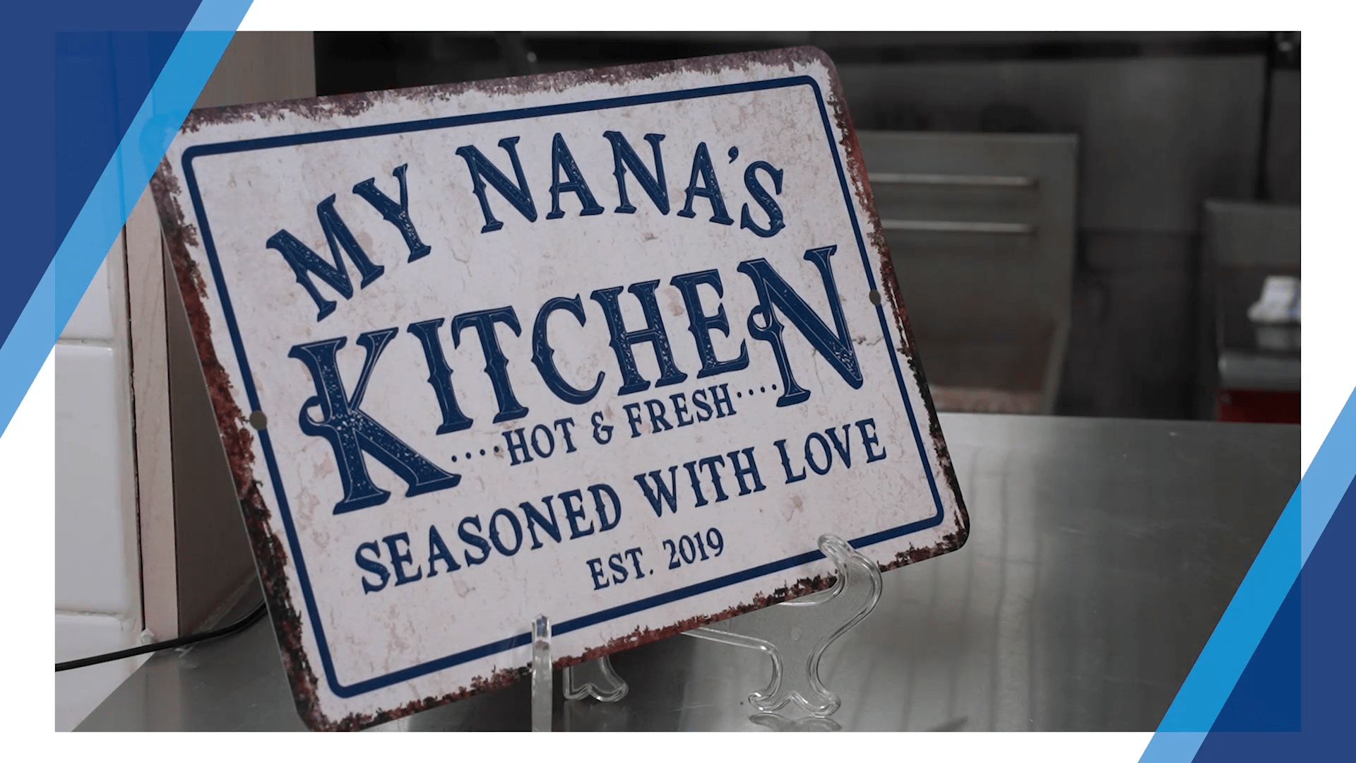 A white sign with dark blue text that reads: My Nana's Kitchen, ...Hot & Fresh..., Seasoned With Love, Est . 2019