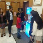 Allendale Attendance Champion, 5th grader Carlan Samuels, cuts the ribbon on the newly installed FloWater hydration station in the school cafeteria. He's flanked by (L-R) Mayor Libby Schaaf, Superintendent Kyla Johnson-Trammell, Allendale Principal Desiree Miles, County Supervisor Wilma Chan, OUSD Board of Education President Aimee Eng and Larry Brooks from the County's Healthy Homes Department.